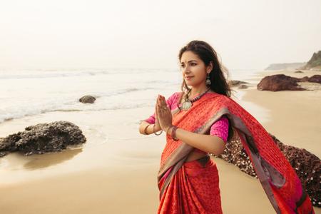 Indische vrouw in traditionele saree kleren bidden op de aard met zonsondergang op de achtergrond Stockfoto