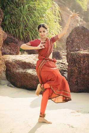Schöne indische Frau im roten Sari tanzen traditionellen Bharatanatyam Tanz Standard-Bild