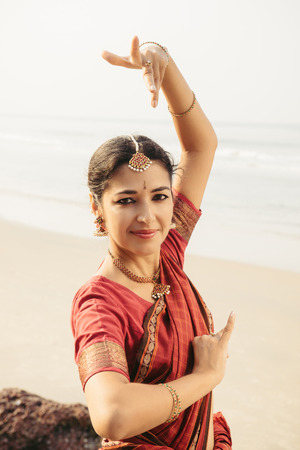 bharatanatyam dance: Beautiful indian woman in red saree dancing traditional Bharatanatyam dance Stock Photo