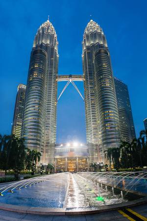 megalopolis: Kuala Lumpur, Malaysia - March 16, 2016: Night Petronas towers in Kuala Lumpur. Urban asian megalopolis on blue sky background, Malaysia