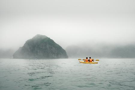 lifejacket: Couple paddling the kayak in mist weather. Ha Long Bay, Vietnam, Cat Ba Island