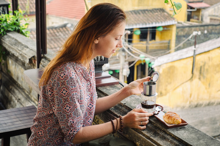 Young woman drinking vietnamese coffee in cafe in Hoi An city, Vietnam Imagens