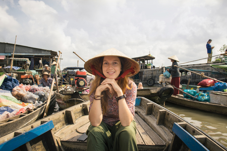 Woman tourist riding on a boat on Cai Rang floating market, Can Tho, Vietnam