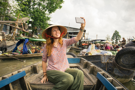 can tho: Woman tourist take selfie photo from the boat on Cai Rang floating market, Can Tho, Vietnam Stock Photo