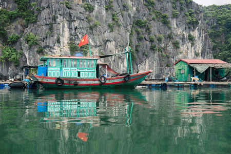 halong: Fishing boat with the flag of Vietnam reflacting in sea water in the Halong Bay at the Gulf of the South China Sea, Vietnam Editorial