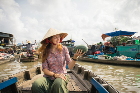 cai: Woman tourist buying fruits from the boat on Cai Rang floating market, Can Tho, Vietnam