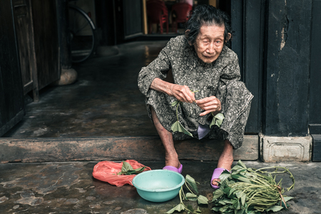 non la: Hoi An, Vietnam - April 5, 2016: Portrait of old vietnamese woman near the own house in Hoi An city