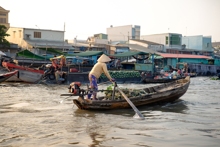 can tho: Can Tho, Vietnam - April 2, 2016: Vietnamese Woman on a boat on Cai Rang floating market in the Mekong Delta Editorial