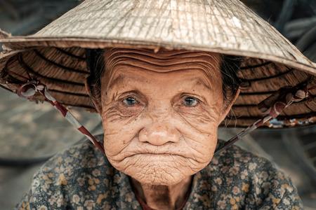 non la: Hoi An, Vietnam - April 5, 2016: Portrait of old sad vietnamese woman on the street in Hoi An city