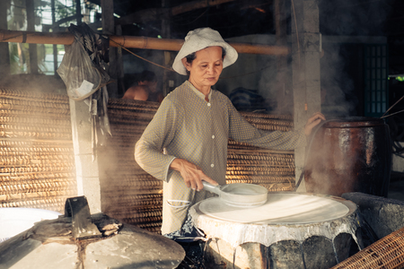 can tho: Can Tho, Vietnam - April 2, 2016: Senior woman working on homemade rice macaroni factory in Vietnam