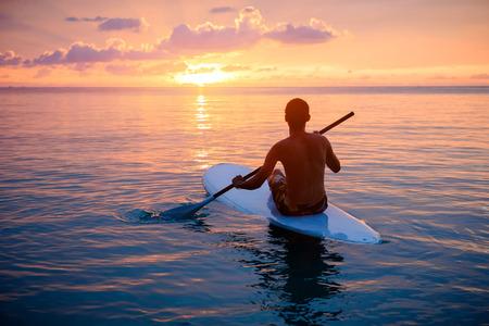 Silhouet van de mens peddelen op paddle board bij zonsondergang. sport water in de buurt van het strand op zonsondergang Stockfoto