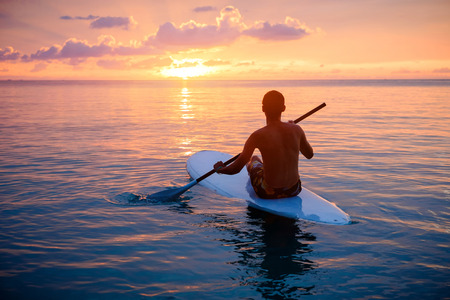 Silhouette of man paddling on paddle board at sunset. Water sport near the beach on sunset