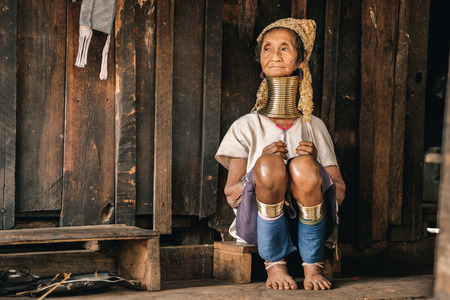 Pan Pet, Myanmar - May 25, 2016: Portrait of Padaung (Karen) long neck woman in brass rings around their neck and traditional clothing near the house