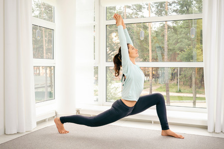 Young woman doing yoga exercises at home with big windows on background