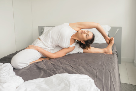 Young woman gets up and doing morning yoga exercises in bed. Healthy lifestyle concept Imagens