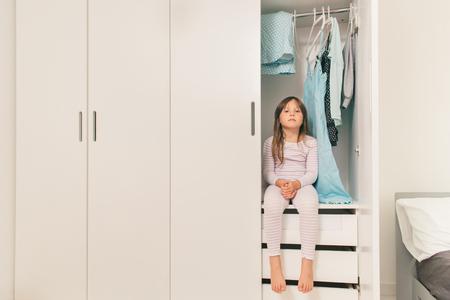 petite fille triste: Seul petite fille triste assis dans la garde-robe de la m�re. Concept: probl�me de choisir des v�tements pour femmes