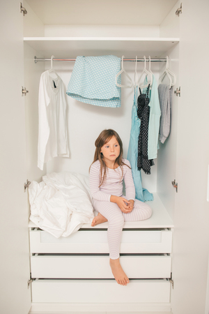 sad little girl: Alone sad little girl sitting in mothers wardrobe. Concept: problem to choose clothes for female Stock Photo