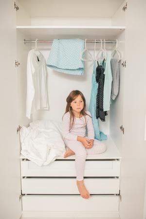 petite fille triste: Seul petite fille triste assis dans la garde-robe de la mère. Concept: problème de choisir des vêtements pour femmes