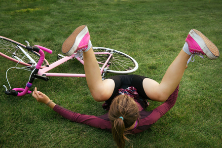 Woman fall down from the bicycle on the back. Active lifestyle.