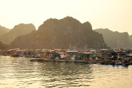 cay: House and fishing boat in Cay Beo floating village on sunset, Ha Long Bay, Vietnam