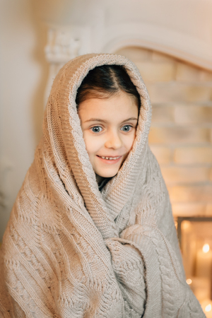 Cute little girl sitting near fireplace in the evening and covered in warm scarf waiting for Christmas. Cold winter weekends. Cozy scene Stock Photo
