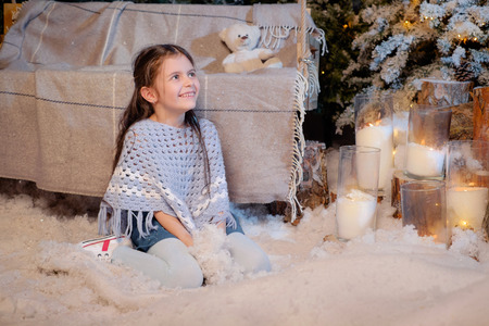 Beautiful smiling little girl playing near the christmas tree. Room decorated for New Year. Holiday atmosphere.