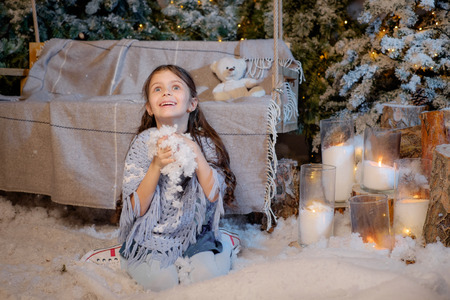 Beautiful smiling little girl playing near the christmas tree. Room decorated for New Year Stock Photo