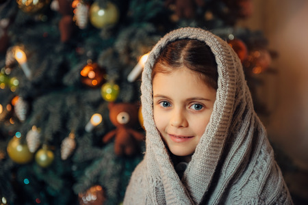 Cute little girl sitting near christmas tree in the evening and covered in warm scarf waiting for holiday. Cold winter weekends. Cozy scene