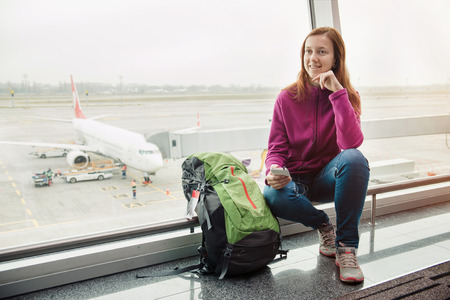 airport window: Tourist woman sitting near airport window with her backpack and listening music on mobile phone Stock Photo