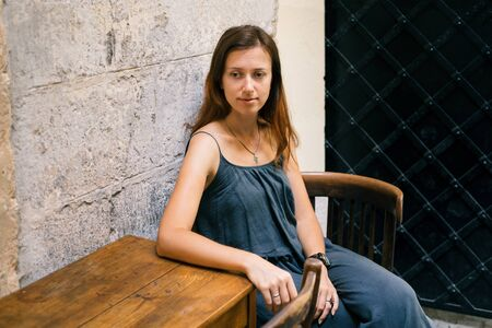 lvov: Young woman sitting by the wood table in cafe with old minimalism design on historical Lvov city