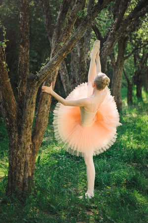 Young ballerina in pink tutu stretching her legs and doing exercise on the green forest before dance