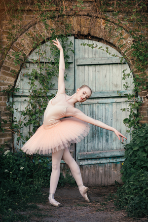 Young woman with perfect body in white tutu dancing outdoors with urban background. Beautiful ballerina showing classic ballet poses and jumping high into the air Stock Photo