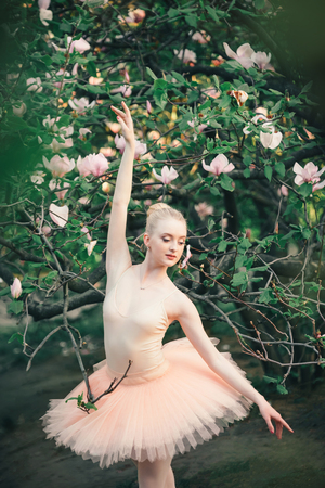 Young woman in white tutu dancing among magnolia flowers landscape. Beautiful ballerina showing classic ballet poses. Concept of female tenderness and harmony life