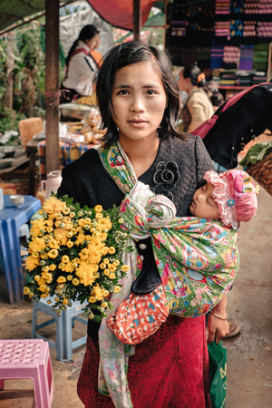 Kalaw, Myanmar - May 23, 2016: Portrait happy burmese woman with her child on the street market in Burma