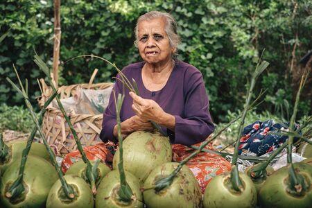 Kalaw, Myanmar - May 23, 2016: Authentic burmese woman selling fresh fruits on the street market in Burma.