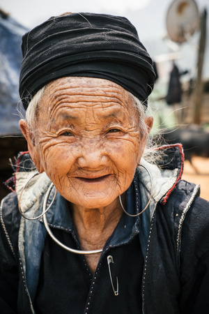 Sapa, Vietnam - April 14, 2016: Old vietnamese woman portrait outdoors in village near Sapa. Black Hmong minority woman in traditional clothes. 新聞圖片