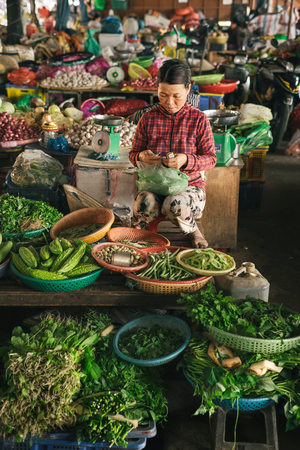 Hoi An, Vietnam - April, 04, 2016: Vietnamese woman in ancient Hoi An town selling local seafood and vegetables on street market