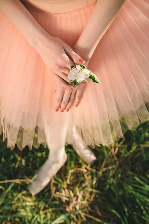 inspiring: Ballerina in white tutu and pointe shoes stay in green nature and holding flower in the hands at sunset. Concept of female tenderness and harmony life