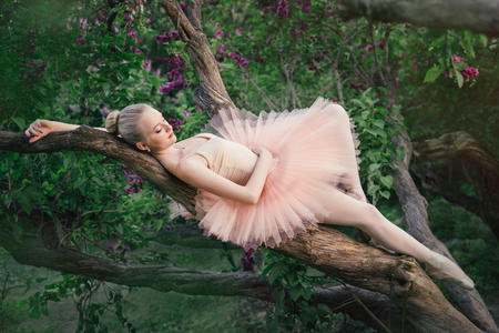 Tender and romantic ballerina woman relaxing and lying on a tree branch in green flowers garden at sunset. Concept of female tenderness and harmony Stock Photo