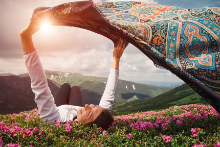 Woman feel freedom lying in blooming rhododendron valley with fluttering tissue in hands on sunset