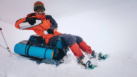 Man with backpack and snowshoes hiking in winter mountain and stopped to have rest and drink hot tea from flask Foto de archivo