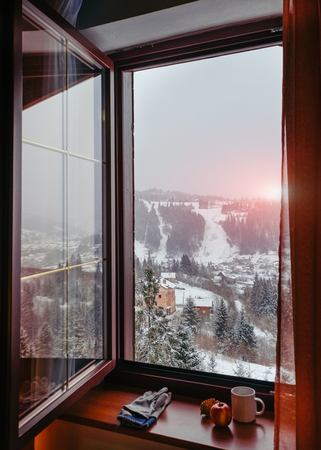 Open window of warm cottage overlooking sunrise at mountain village Banque d'images