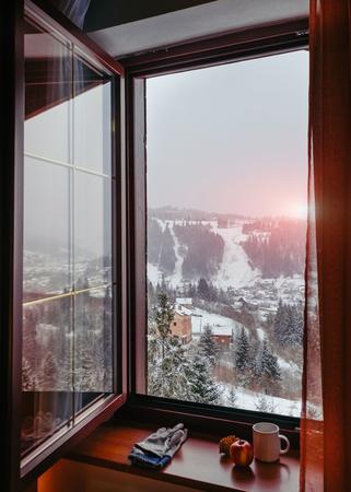 Open window of warm cottage overlooking sunrise at mountain village Stockfoto
