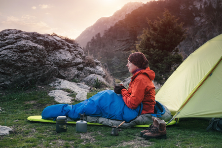 Traveler sitting on the ground next to tent holding cup with coffee in her hands