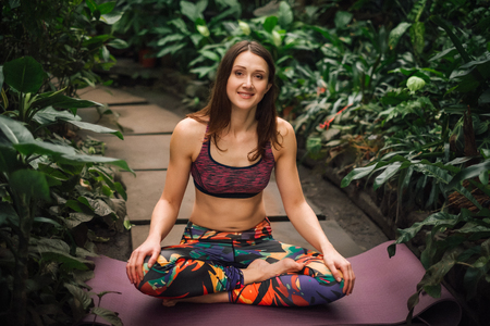 Beautiful barefooted female yoga instructor in a colorful outfit sitting in a easy pose, relaxing on a mat at greenhouse.Looking at camera. Healthy lifestyle concept.