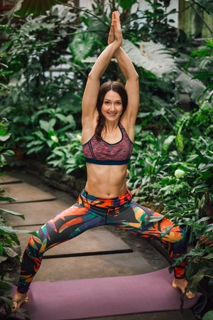 Beautiful barefooted female yoga instructor in a colorful outfit standing in a goddess pose at botanical garden.Looking at camera. Healthy lifestyle concept. Stock Photo