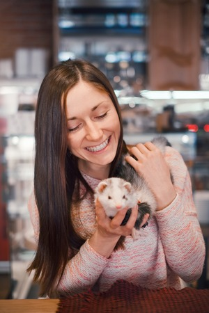 Smiling woman with long chocolate hair holding her pet ferret in hands in a cafe. Woman and a pet concept.