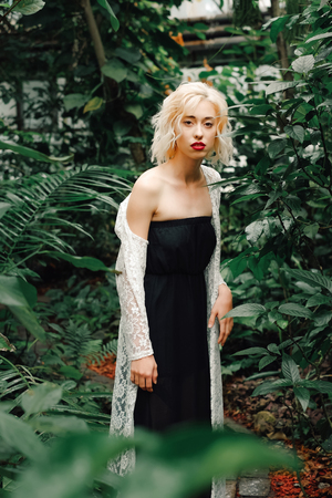 Portrait of beautiful slender female model with perfect curly blonde hair wearing black dress and white lace cardigan revealing one shoulder. Looking at camera, standing in a tropical rainforest.