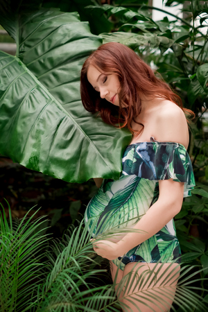 Tender young redhead in a floral swimsuit posing with her head tilted next to the giant leaf at tropical forest, holding belly in arms, side view. Pregnancy and expecting concept. Stock Photo