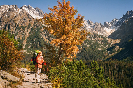 Happy caucasian female tourist enjoying beauty of surrounding mountain life panorama, standing on a stone path leading to Popradske pleso on a sunny day in Slovakia. Shot with film camera and grain Stock Photo
